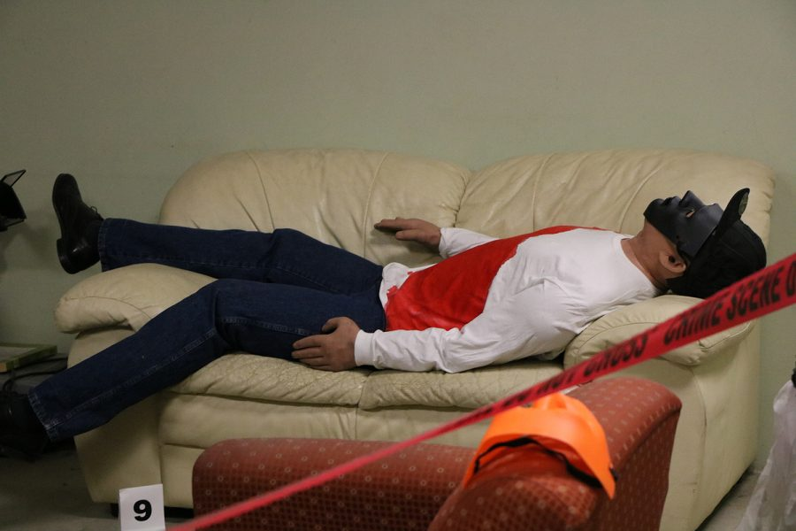 The mannequin lays on the couch behind the red tape for a Halloween party gone wrong during a crime lab for Forensic class.