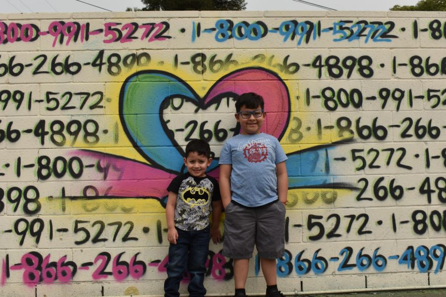 Maverick (left) and Makakai Gonzalez (right) with their father, Hugo Gonzalez's mural.