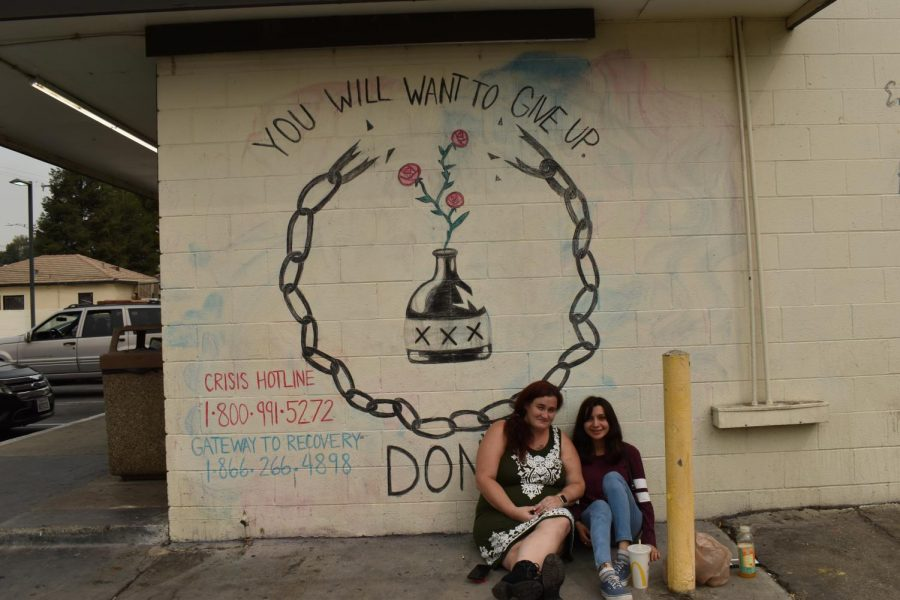 Sarah Collver and Erica Toledo with one of the the several murals part of the Chalk Walk Scavenger Hunt on Sept. 11.