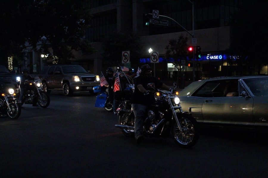 Participants on motorcycles showing there respect by attaching an American Flag to their bike. Side right of the photo shows a 1964 Buick Riviera.